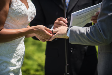 Bride slides diamond ring onto her husband's finger as official looks on during wedding ceremony at alter.