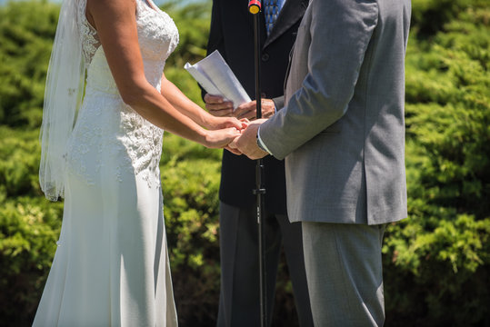 Man and woman at alter with officiate to say their vows in the wedding ceremony.