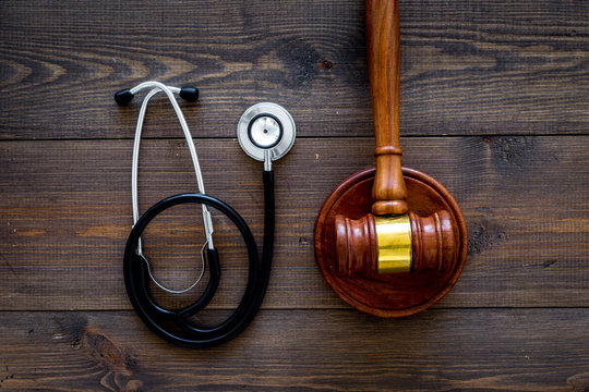 Medical law, health law concept. Gavel and stethoscope on dark wooden backgound top view