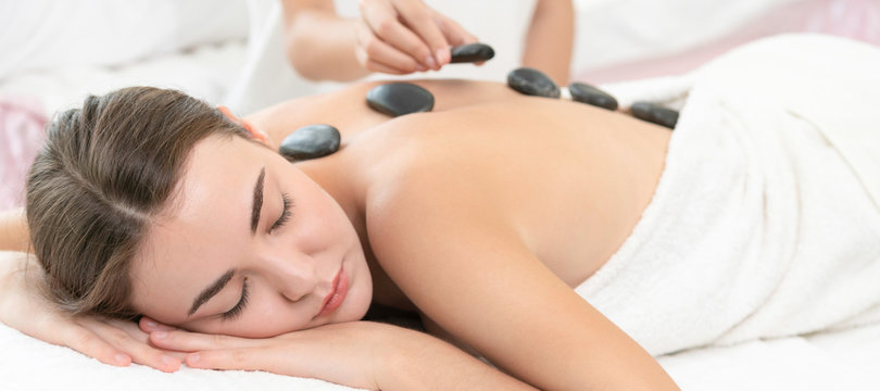 Hot stone massage treatment by therapist in spa.