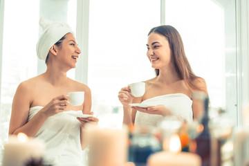 Two women drinking tea in luxury day spa.