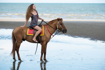 Woman fashion model riding a horse on the beach.