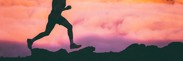 Trail runner legs of man athlete running on rocks in sky pink clouds background. Panoramic banner...
