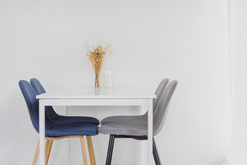 Empty office desk and chair in white meeting room decorated with dry flower.