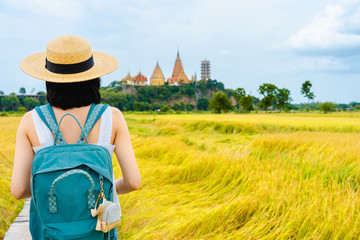 Young asian tourist woman wearing bamboo hat green backpack walking in rice field looking famous landmarks wat tham sua Kanchanaburi Thailand in holiday. Travel vacation concept.