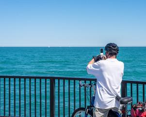 man on bike taking photo of Lake Michigan
