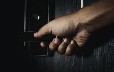 hand opening the door in the dark