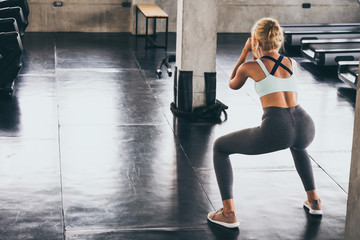 Back view of Young woman doing squat exercise at the gym.