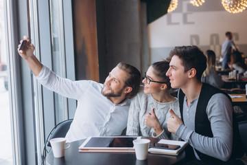Three successful business people taking Selfie
