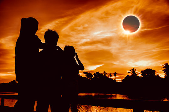 Natural phenomenon. Three person looking at total solar eclipse.