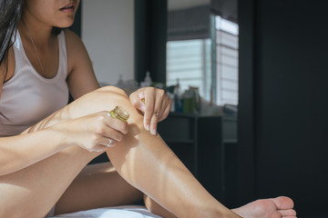 Woman with rash and hands applying cream on her leg from allergies,Health allergy skin care problem