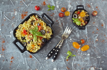Eggplant, olives and tomato Elbow macaroni pasta, on a black serving platter, garnished with fresh basil