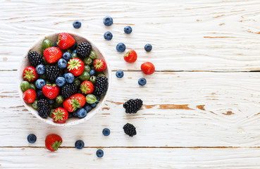 Fresh juicy ripe berries in a white plate-strawberries, blueberries, blackberries and gooseberries