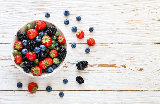 Fresh juicy ripe berries in a white plate-strawberries, blueberries, blackberries and gooseberries