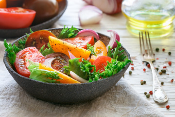 Delicious summer salad of colorful (yellow, red and black) ripe tomatoes, red onions and lettuce with spices. Healthy dinner or lunch