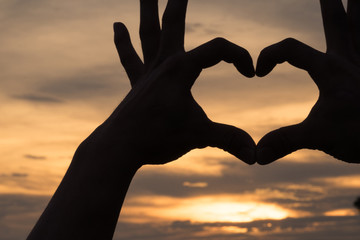 Hands as heart shape with beautiful sky in warm color twilight sunset background,love and romantic concept.