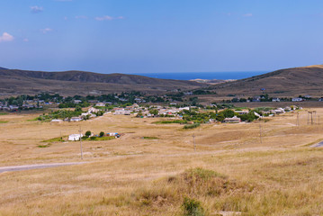 the town spread out in a valley covered with dry yellow grass, on which the road runs along the background of the hills