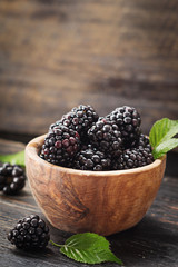 Blackberries in wooden bowl on old dark table with free text space.  Agriculture, Gardening, Harvest Concept. Selective focus.