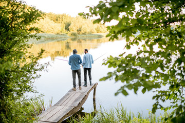 Two male friends fishing together standing on the wooden pier during the morning light on the beautiful lake