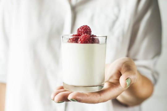 A glass jar with homemade yogurt with raspberries in the hands of a woman in a white shirt. Healthy dietary summer breakfast