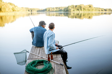 Ingelijste posters Vissen Two male friends dressed in blue shirts fishing together with net and rod sitting on the wooden pier during the morning light on the lake