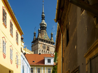 The clock tower from Sighisoara as seen from a street with colorful houses from the medieval fortress