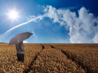 Frau mit Schirm bedauert Dürre und Trockenheit in der Landwirtschaft