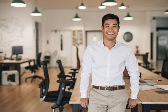 Smiling Asian businessman leaning on a table in an office