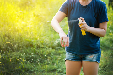 Woman applying insect repellent before forest hike beautiful summer day.