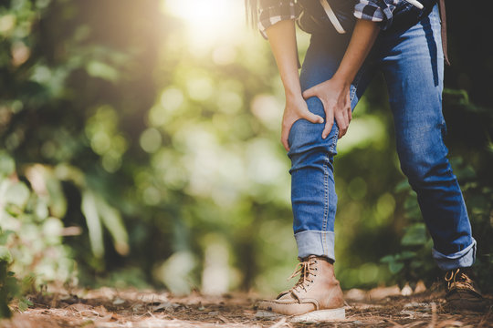 Women are injured at the knees after hiking. Hiking concept.