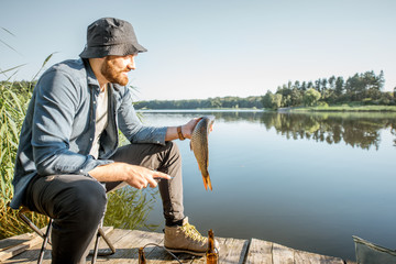 Printed kitchen splashbacks Fishing Portrait of a handsome fisherman with fish on the wooden pier near the lake in the morning