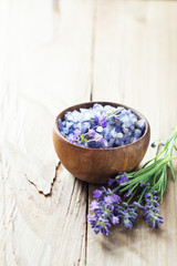 Lavender salt with flowers on wooden table.