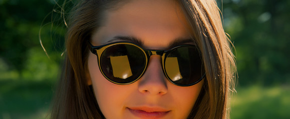 portrait of a girl wearing sunglasses against a forest background.