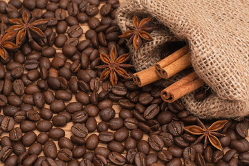 Background of coffee beans. Coffee texture. Cinnamon sticks and cardamom.