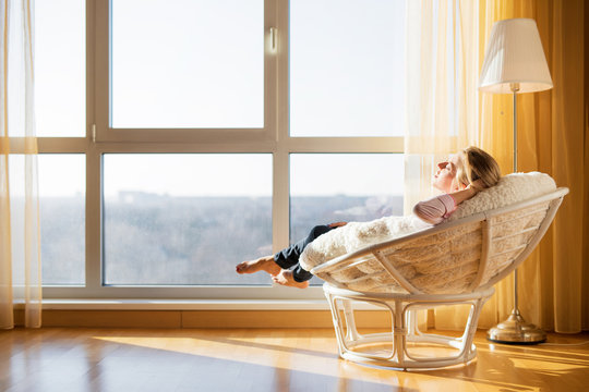 Woman relaxing in chair by the window