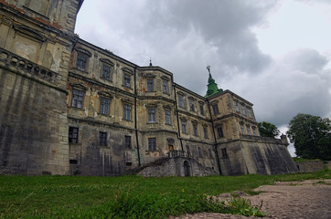 Medieval Pidhirtsi Castle at cloudy summer day, several minutes before rain. Village Pidhirtsi, Lviv region, Ukraine. Selective focus with wide angle lens