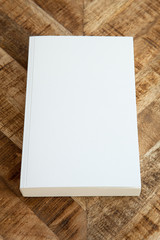 A white book with a blank cover on vintage wooden table.