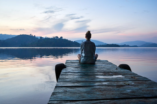 Woman sitting on dock at sunset on Lake Bunyonyi, Uganda, East Africa