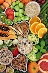 High dietary fibre health food concept with fresh fruit, vegetables, whole wheat pasta and cereals with foods high in antioxidants, anthocyanins, smart carbohydrates and vitamins. Top View.