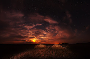 Night photo. Straws of straw on the cleaned field and starry sky with clouds and moon.