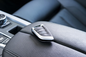 Closeup inside vehicle of wireless key ignition. Start engine key. Car key remote in black perforated leather interior. Modern car background. Modern car Interior details. Car detailing.