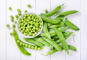 Fresh peas on white wood background. Top view
