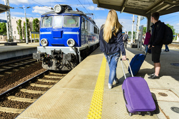 hipster girl with suitcase waiting for train on platform