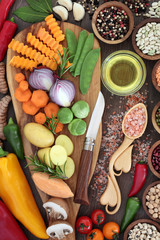 Healthy food concept with fresh vegetables, herbs, spice, pulses, olive oil and himalayan salt in a wooden lovespoon. Super foods  high in antioxidants, anthocyanins, minerals and vitamins.
