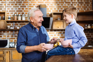 Positive aged man enjoying breakfast with his grandson