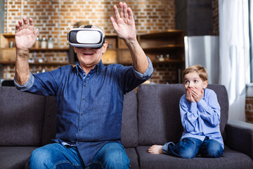 Smiling elderly man wearing VR glasses