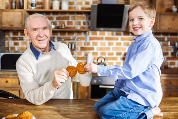 Nice little boy eating cookies with his grandfather