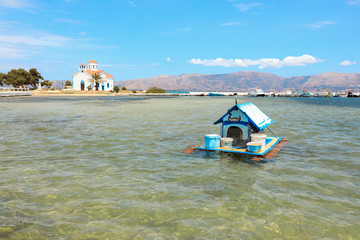 House for ducks on the water in the Elafonisos village on the background of Agios Spyridon church and picturesque seascape. Elafonisos island, Laconia, Peloponnese, Greece June 2018.