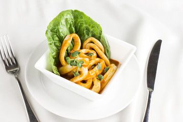 Squid rings in sauce with greens in deep white plate on serving table