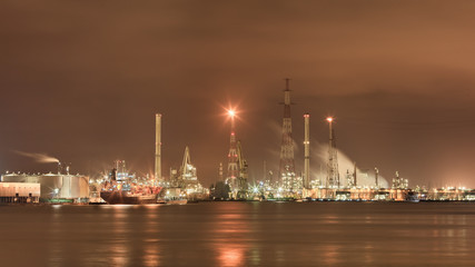Landscape of the vast harbor area with Illuminated petrochemical production plant, Antwerp, Belgium.